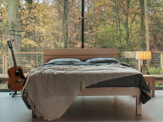 A striking bedroom with woodland view featuring our Tibet wooden bed