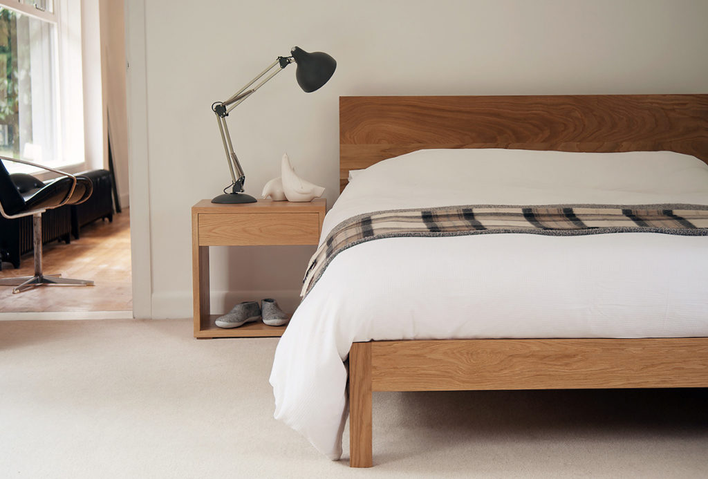 A modern solid wooden bed - the Malabar in Oak and shown with Oak Bedside Cube table