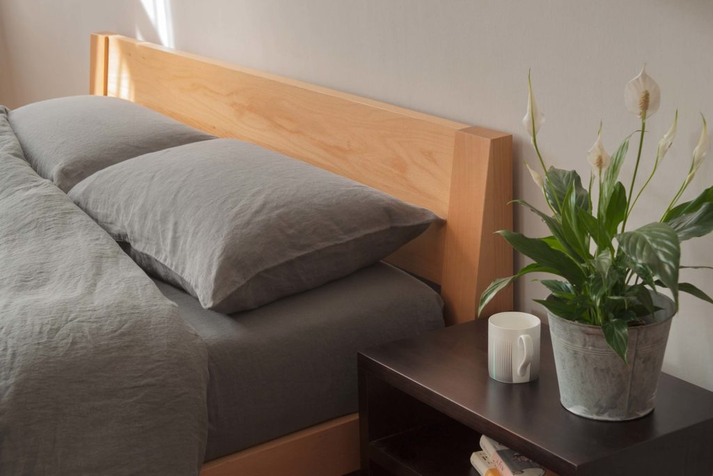 Java is a contemporary low solid wooden bed with a slanted headboard