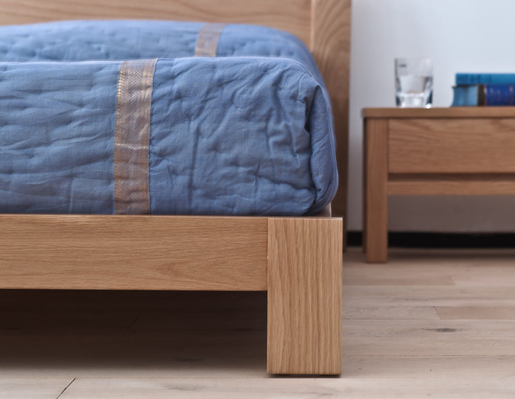 Close up of the leg of the Java low wooden bed in solid oak
