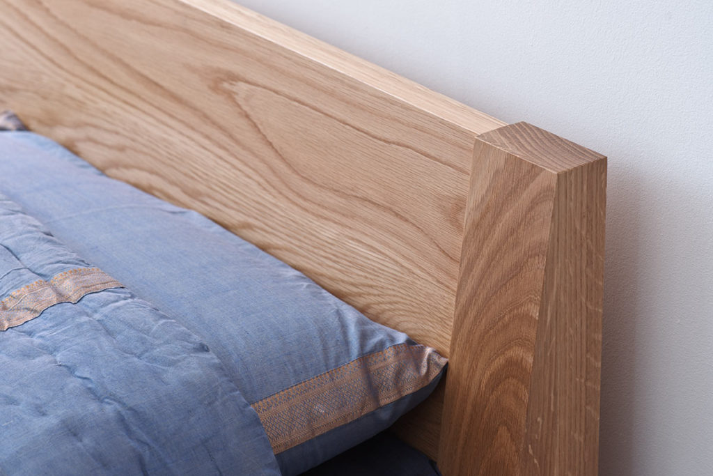 A closer look at the headboard of the Java low wooden bed in solid oak