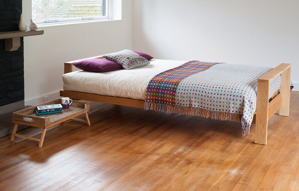 The Cuba Oak futon sofa bed shown in bed position