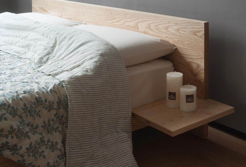 A closer view of the optional attached side tables on our hand made low Kulu wooden platform bed