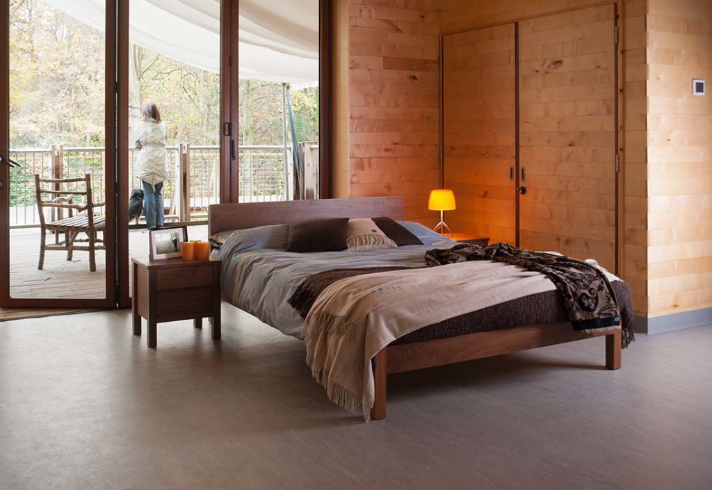 Country bedroom featuring our Sahara contemporary wooden bed in solid walnut with walnut Shaker bedside chest