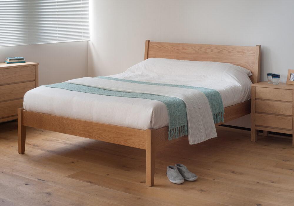Our modern yet classic wooden Zanskar bed shown in Oak