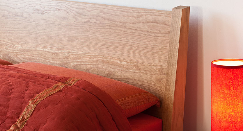 Close up of the sloping headboard of our Zanskar solid wooden bed in Oak