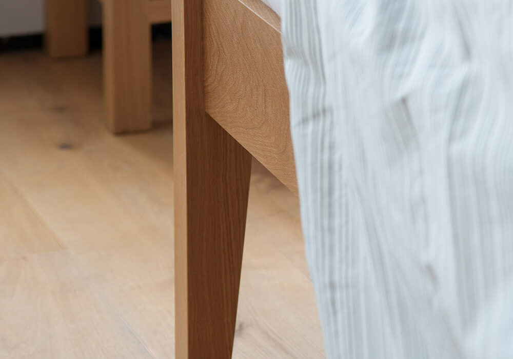A close up of the leg joint of our Zanskar solid wooden bed