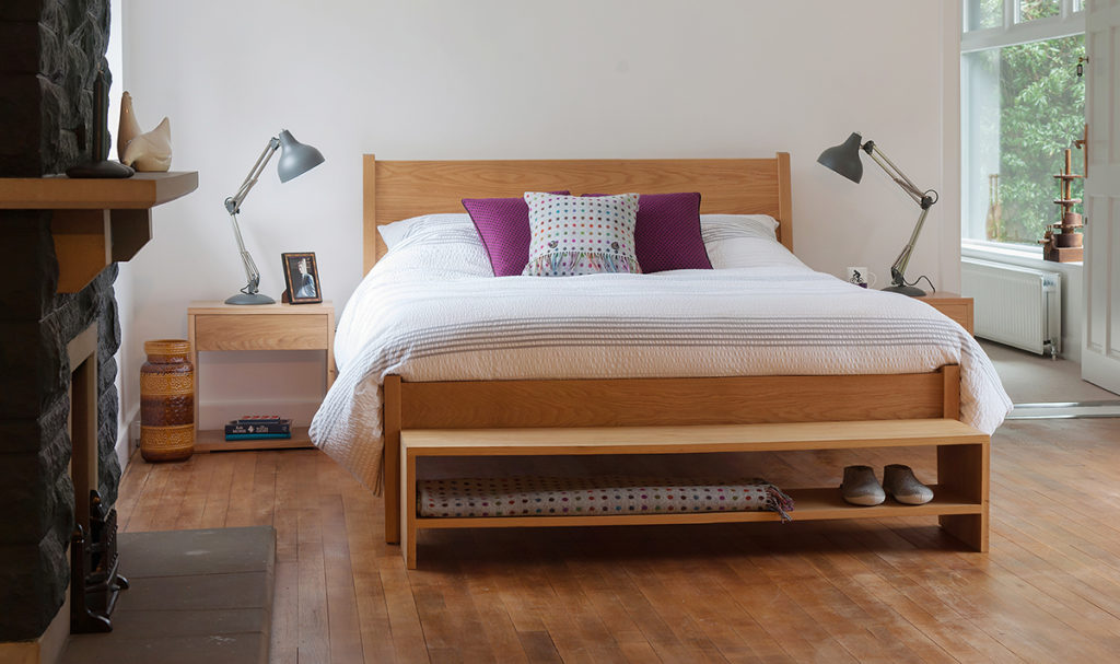 Contemporary bedroom with our wooden zanskar bed, Cube bedside tables, and storage bench, all in Oak.
