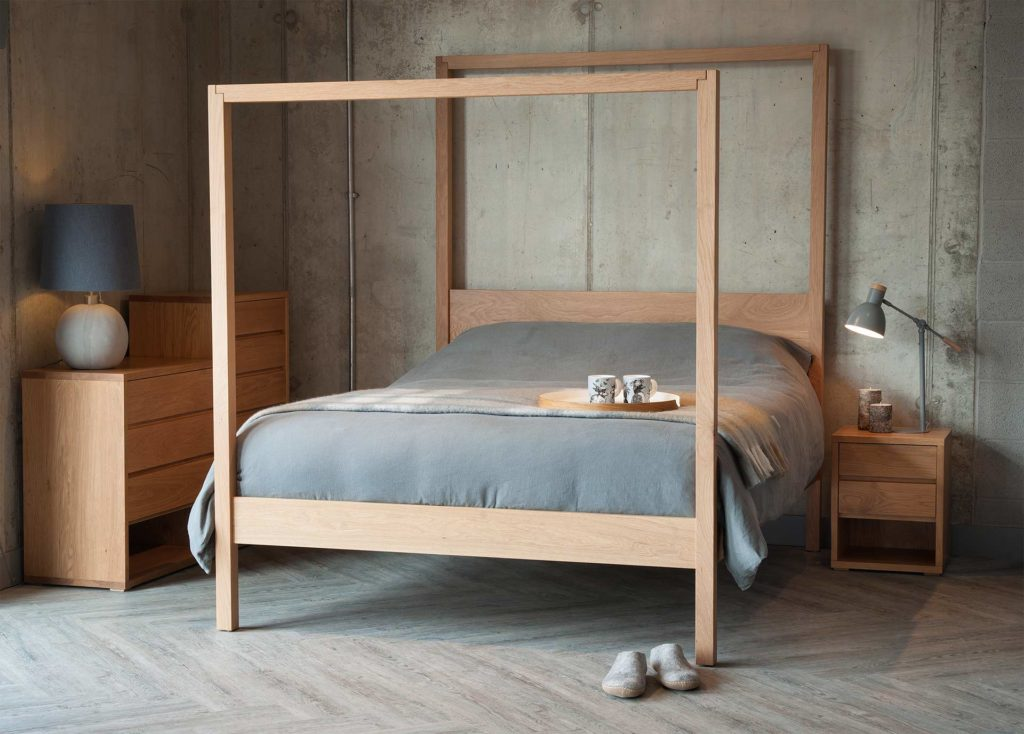 The Oasis a hand made wooden 4-poster bed here in solid oak, shown with black lotus Cube chests of drawers.