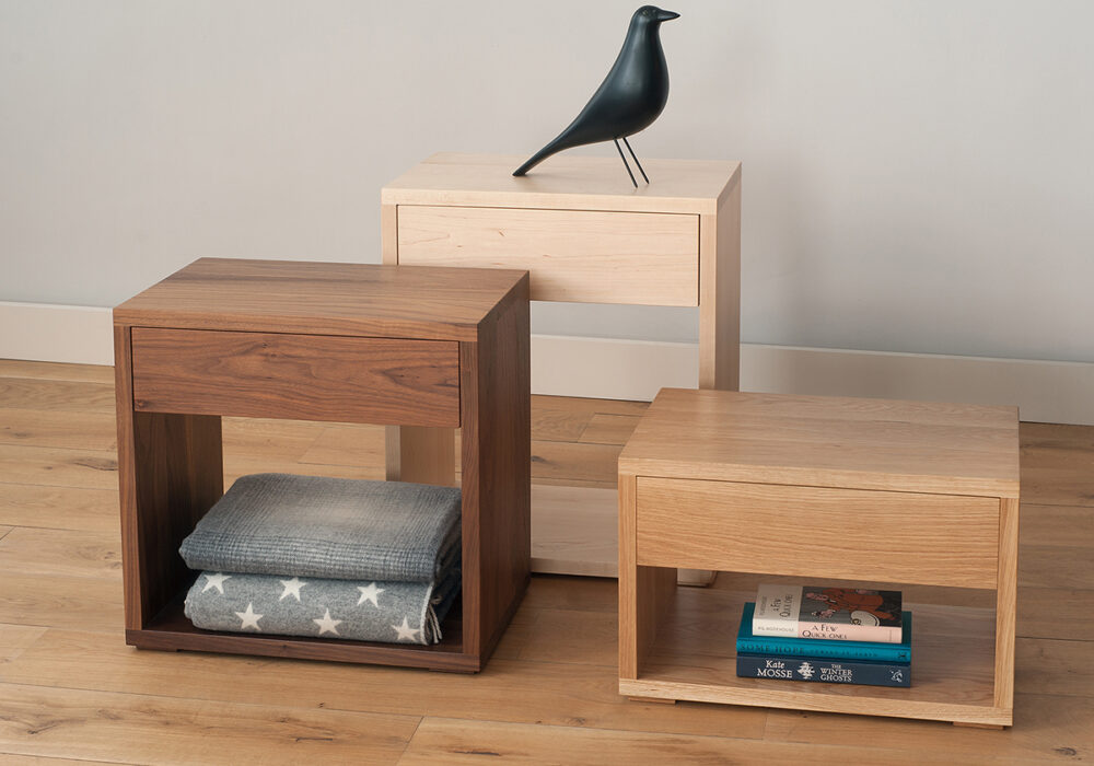 Cube bedside tables with storage drawer in 3 heights and made in a choice of wood.