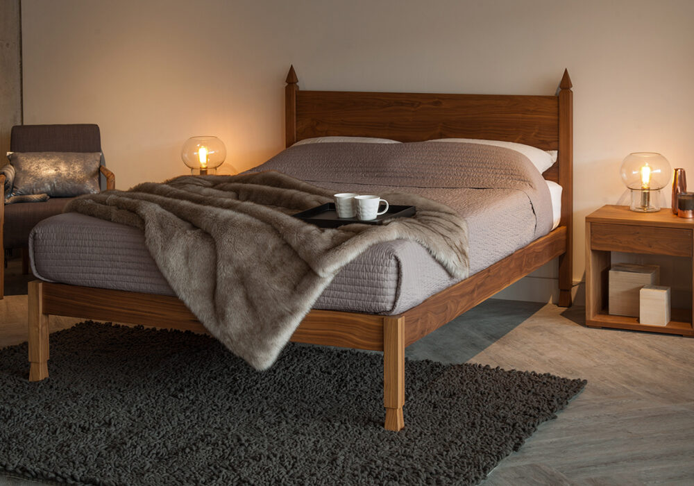 Angled view of the Samarkand Indian inspired walnut bed with hand carved details