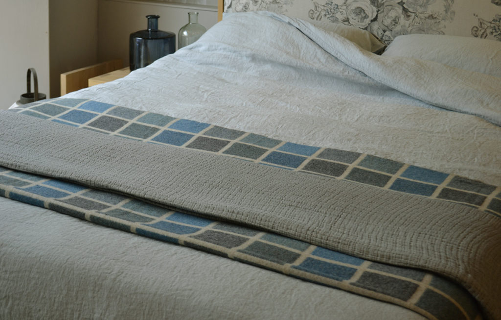 Duck-egg blue linen bedding with a multi-block wool throw, on the Shetland Bed