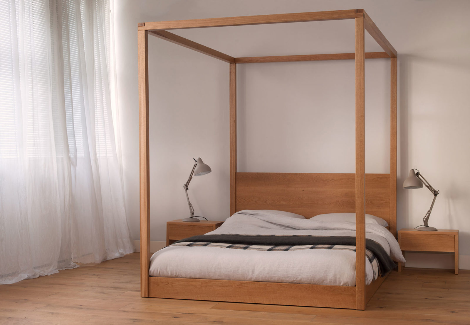 A low modern 4 poster bed, the Cube made by us in UK from solid wood and in a range of sizes.