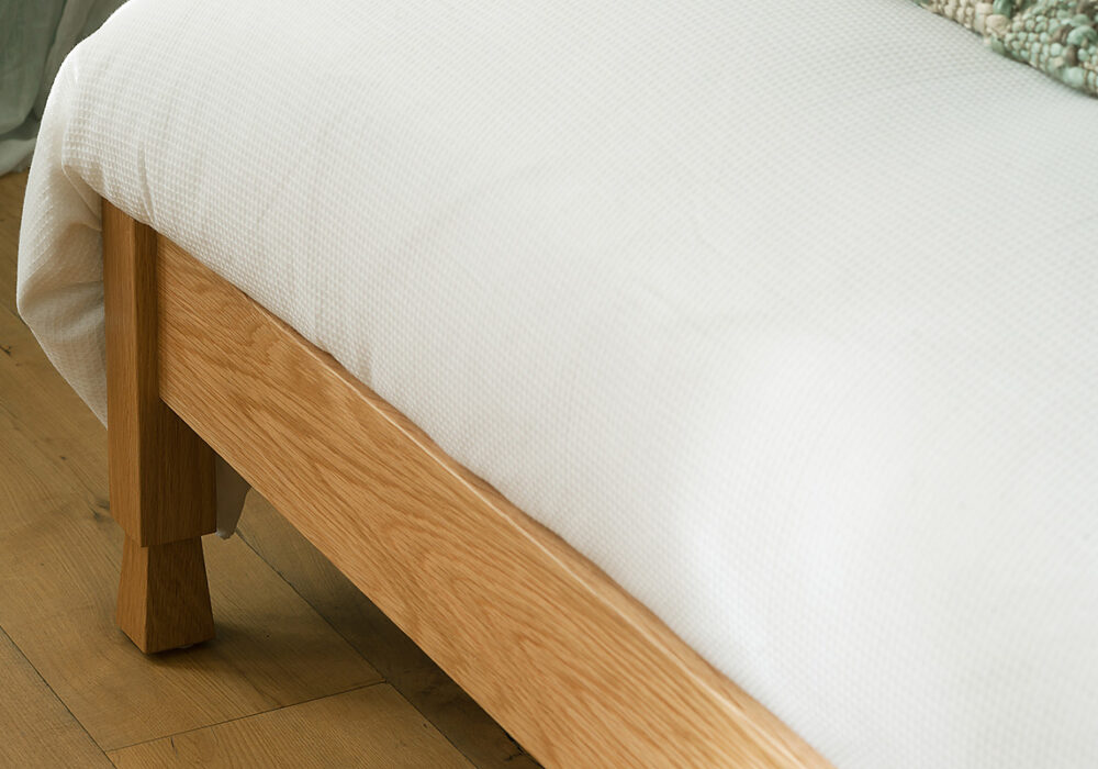 A close view of the carved foot details of the Mandalay Indian style bed
