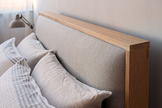 A view of the padded upholstered headboard of our hand made wooden framed shetland bed