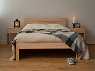 Scandi look maple tibet bed with candles and draped alpaca throw