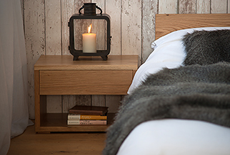A rustic bedroom look simple Oak low Cube bedside table with storage drawer and open bookshelf..