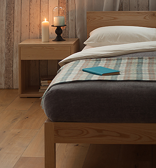 A cosy rustic bedroom featuring our solid wood malabar bed in Ash with Ash bedside Cube table