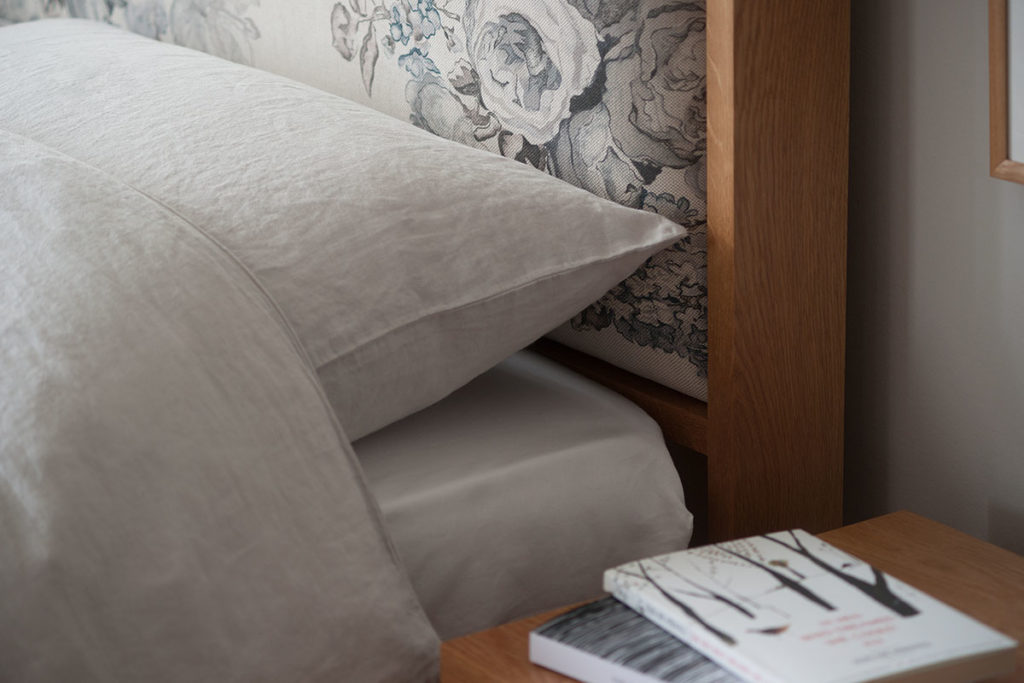Linen bedding against our wooden Shetland bed patterned fabric padded headboard