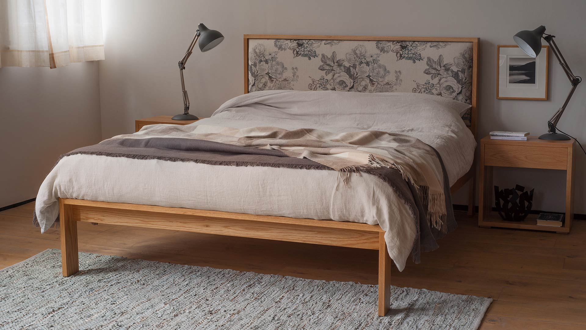 Shetland wooden bed with upholstered headboard shown in oak with Oak Cube tables as bedsides