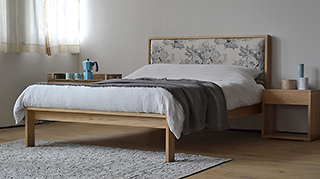 Summer bedroom with solid oak Shetland bed with floral headboard and oak bedside tables