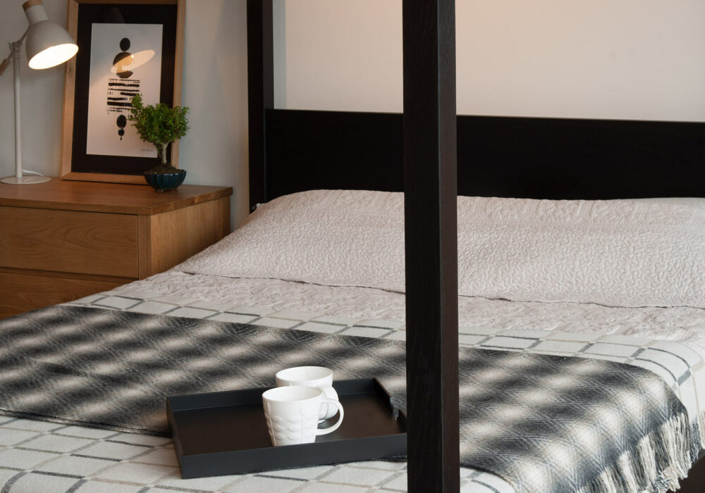 A closer view of our black orchid 4 poster bed with bronte throws and damien tray table
