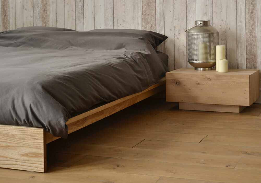 Angled view of our solid wood Ki Bed frame shown with Ethnicraft Madra table as bedside