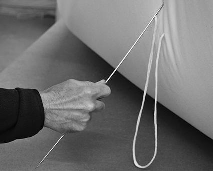 Futon making - our hand made futon mattresses being threaded at our British workshop.