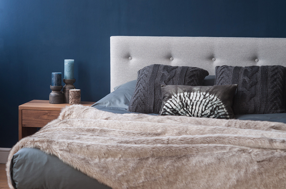 Arran wooden bed padded headboard in grey wool, smoke grey bedding and beige faux fur throw