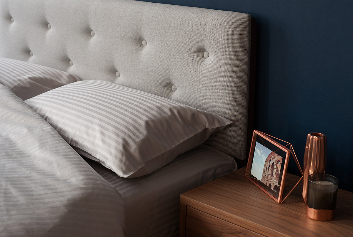 A closer view of the arran wooden bed padded headboard & satin stripe bedding