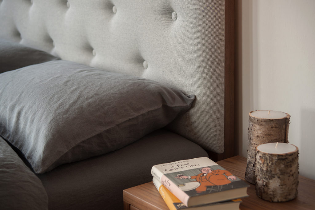 buttoned headboard bed with linen bedding - close up