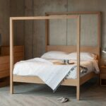 Oasis modern four poster bed hand made from solid wood shown with Oak Cube bedroom storage furniture.