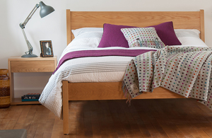 Classic Zanskar a taller solid wooden bed in Oak, made in UK, shown with Oak Cube bedside table.