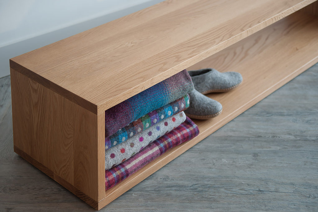 A close up view of the Black Lotus end-of-bed storage bench in Oak wood