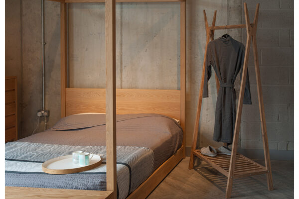 Wooden clothes hanging rail with our Contemporary Cube 4 Poster Bed in Oak