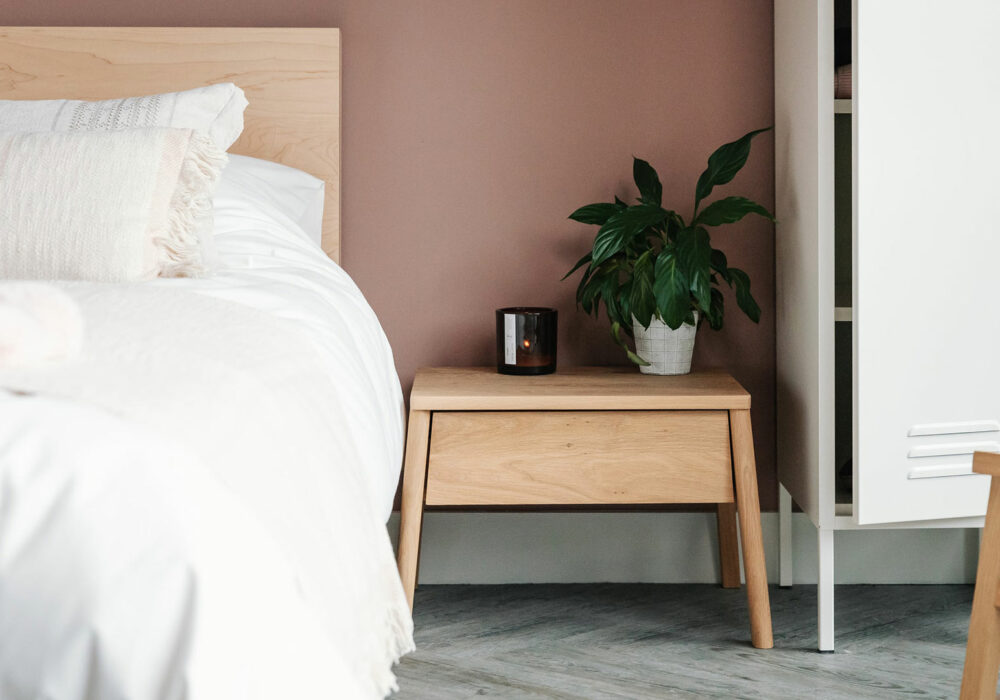 Air bedside table with drawer in oak and shown with Maple Malabar bed