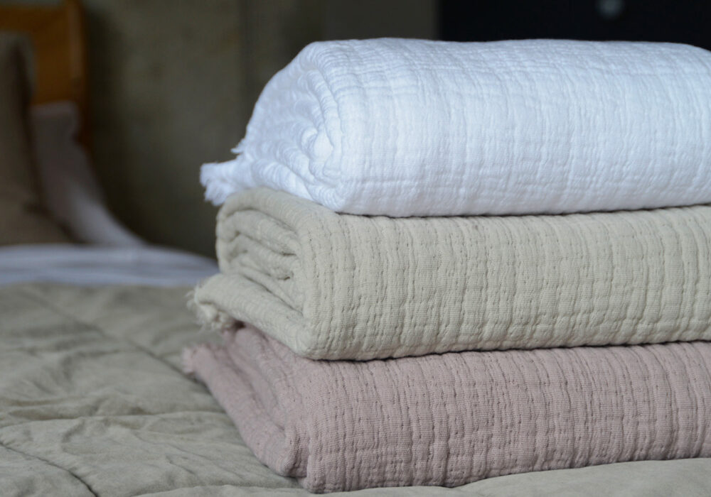 pure cotton crinkled effect throws up close in a stack, in white, stone and blush pink