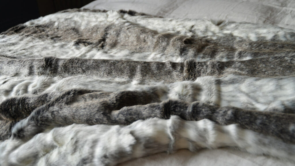 detail view of our softest faux fur arctic fox throw in grey colours and white