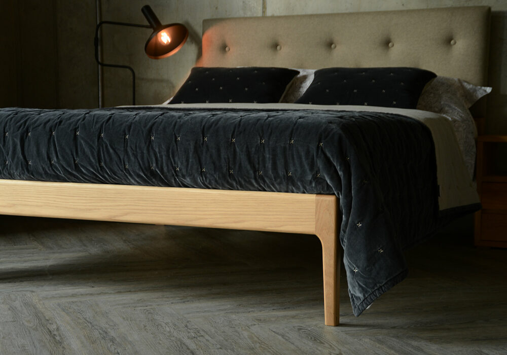 Bloomsbury a solid oak bed with curved legs and an upholstered and buttoned headboard
