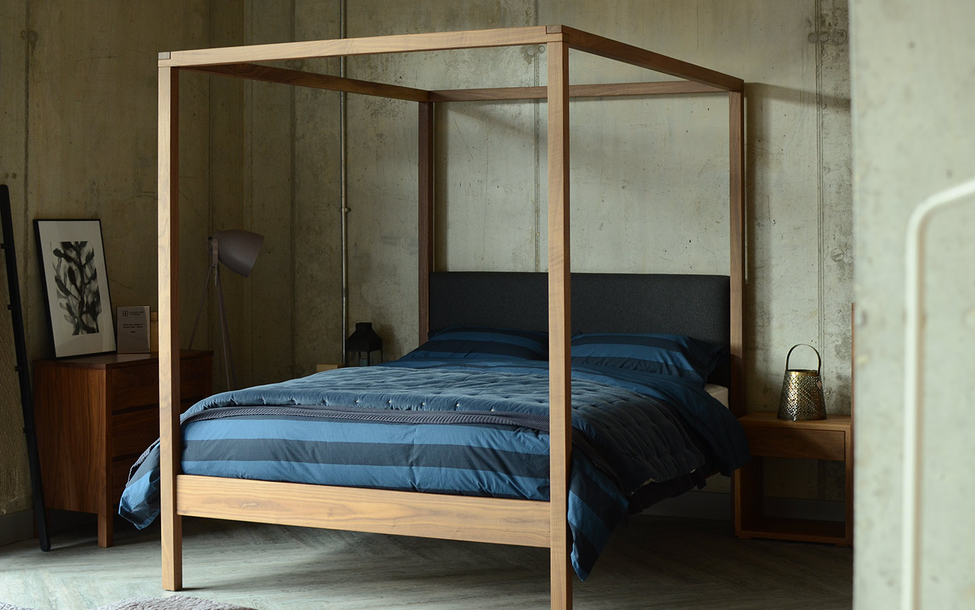 Industrial look bedroom featuring the Highland 4 poster bed in walnut with grey wool padded headboard