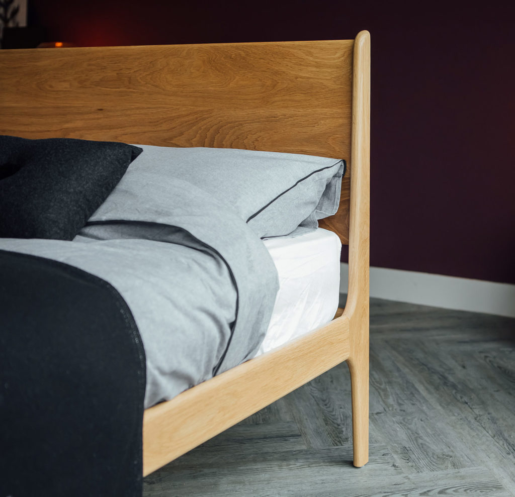A close-up shot of the Camden Bed solid wood Headboard and curving leg