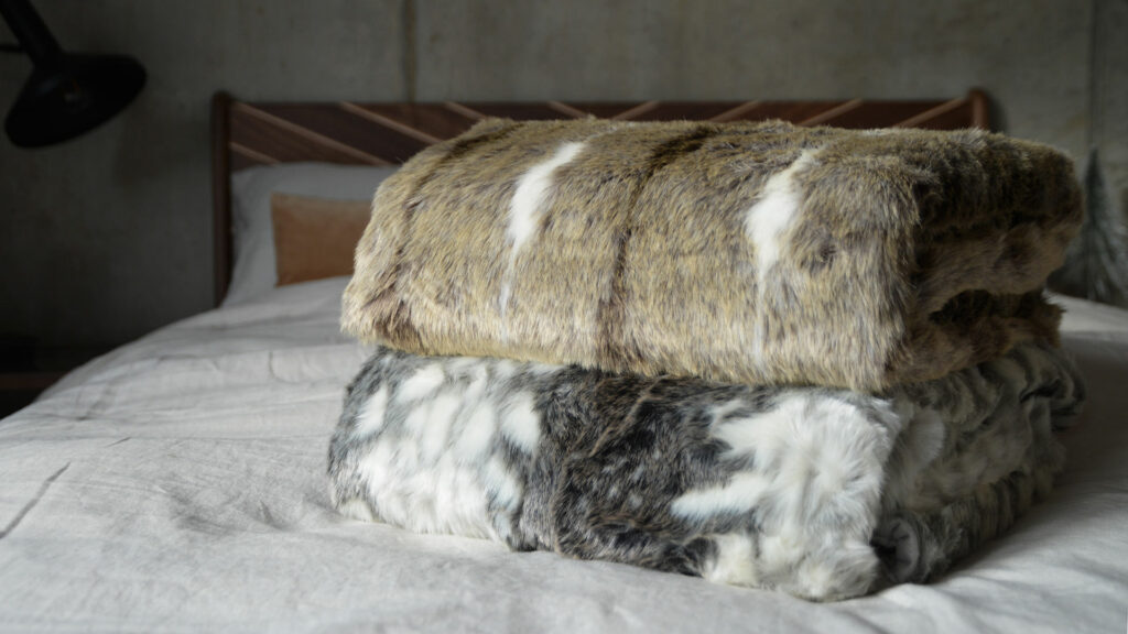 softest faux fur throws in grey or beige colours and white, shown together