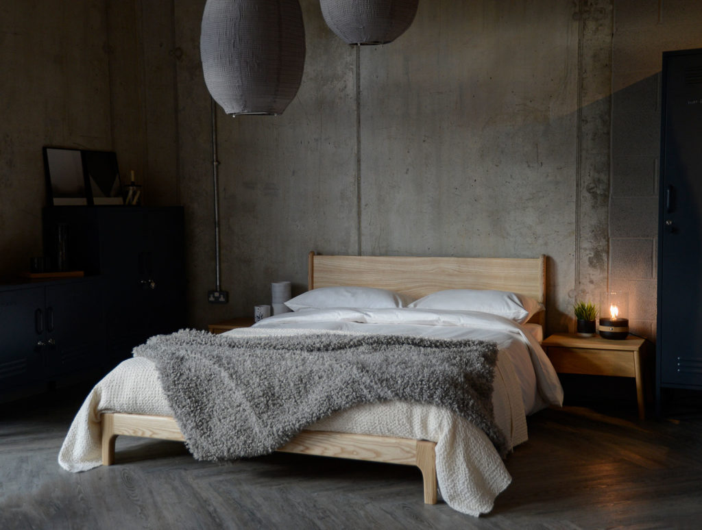 A low hand made Arts and Crafts style wooden bed, in an industrial bedroom setting, the Carnaby in solid ash