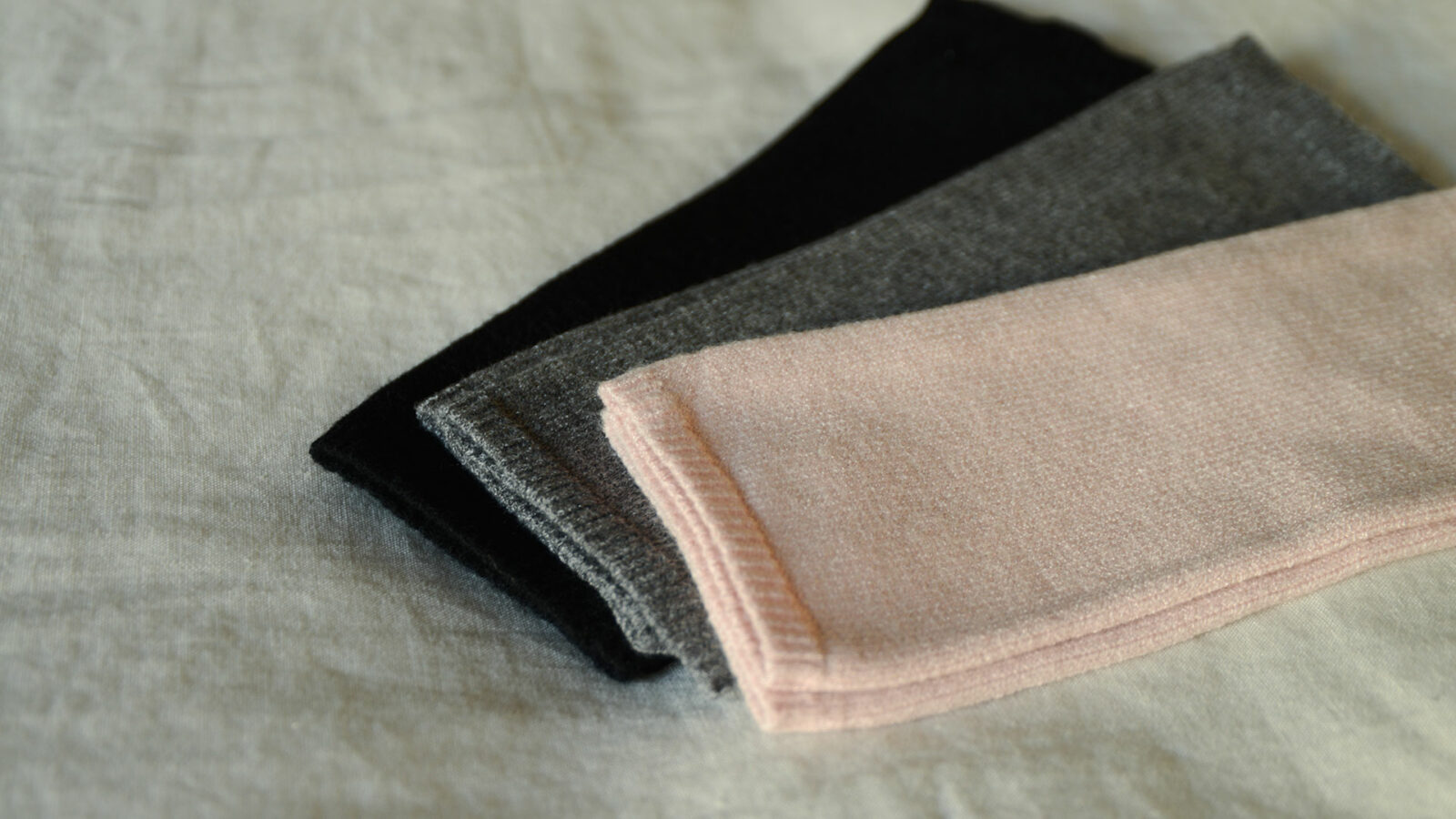 cosy knitted fingerless gloves in black, grey, and blush pink