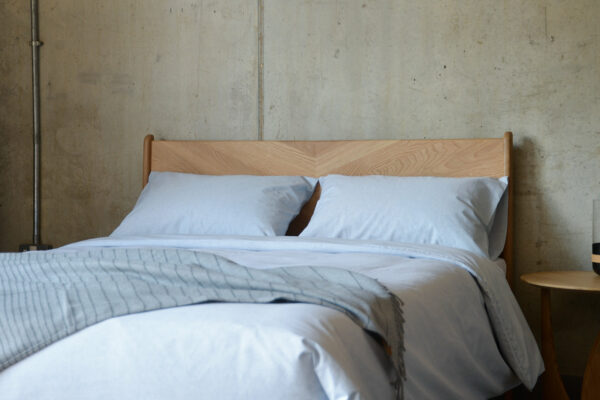 pale blue eco Bedding made from 100% recycled denim fibres shown on our wooden Hoxton bed