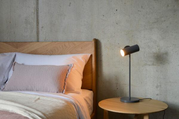 adjustable spotlight in slate grey used as a bedside lamp