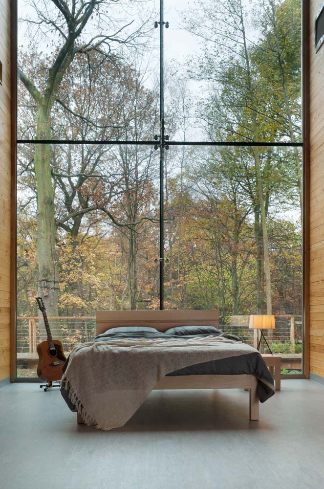 The solid maple Tibet bed with Zebrano stripe in a striking roomset with a glazed wall onto woodland