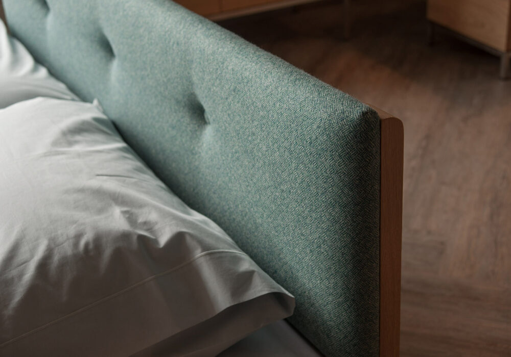 Close view of the Iona low wooden bed buttoned and upholstered headboard