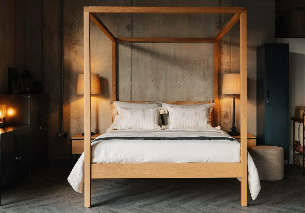Cosy industrial bedroom featuring the hand made solid wooden Kelham 4 Poster bed in Oak