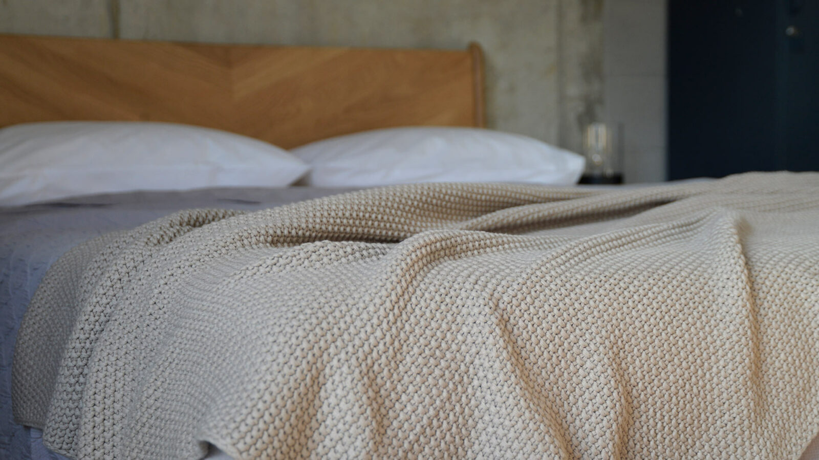 moss stitch knitted cotton throw in taupe shown on a bed